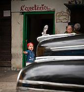 Child framed by classic car in Havana, Cuba