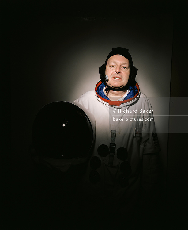 A portrait of space-suited frequent flyer astronaut Alan Watts in his north London home, England. Alan, 51, runs an electrical company and qualified for a free space space flight after being contacted by Sir Richard Branson's Virgin Galactic space company, having accumulated 2 million air miles on the Virgin Atlantic flight network. Aboard the re-usable space vehicle will be 6 passengers, each of whom will have paid $200,000 for the 40 minute flight to 360,000 feet (109.73km, or 68.18 miles) and to experience just 6 minutes of weighlessness. Flights start around 2009/10 from a Mojave desert test facility but therafter, at the new Philippe Starck-designed SpacePort America, New Mexico, USA. a 27 square mile, $225 million headquarters and mission control facility near Las Cruces.  ..