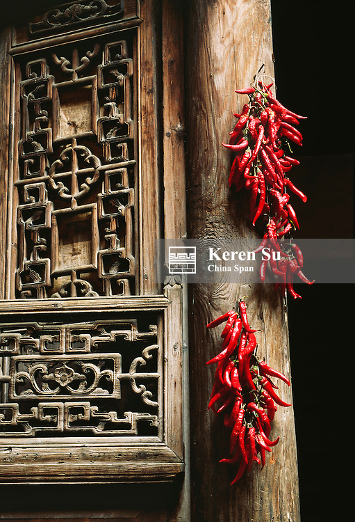 Red pepper on traditional wood door decorated with intricate carving, Anhui Province, China