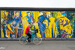 Cyclist rides past a mural painted on original section of Berlin Wall at East Side gallery in Berlin, Germany ...Editorial Use Only