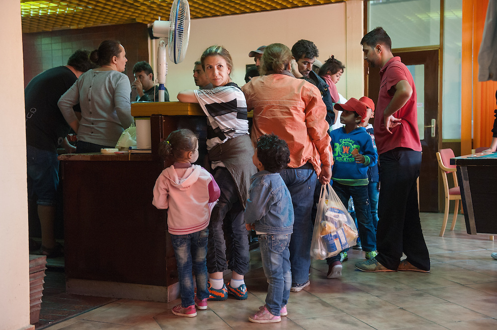 Noon, Monday 14th of September 2015. Aysha buys crisps for the girls at the Bečej bus station. The bus stopped for half an hour and everyone is buying sandwiches and drinks. Before the refugee influx this provincial bus station was very quiet.