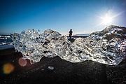 Jökulsárlón, Iceland, 2 apr 2019, A woman jumps over the ice at Jökulsárlón glacier lagoon. The lagoon is young and created by the melting Breiðamerkurjökull glacier.