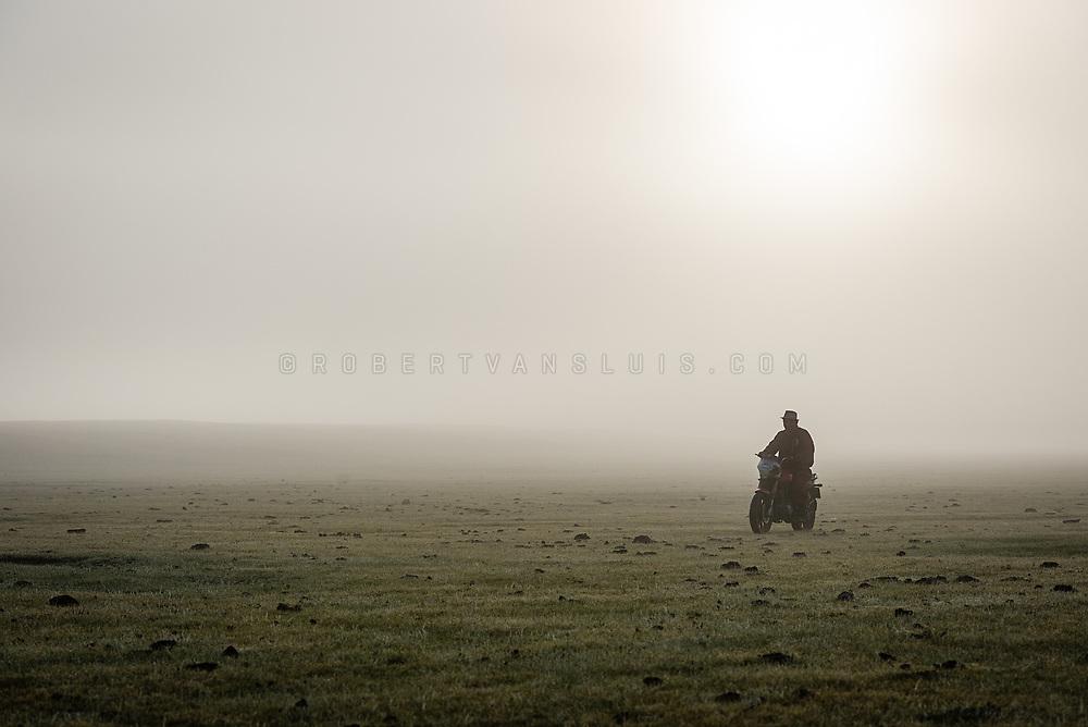 A farmer rides a motorbike in the morning mist in Khovsgol Province, Mongolia. Photo © Robert van Sluis