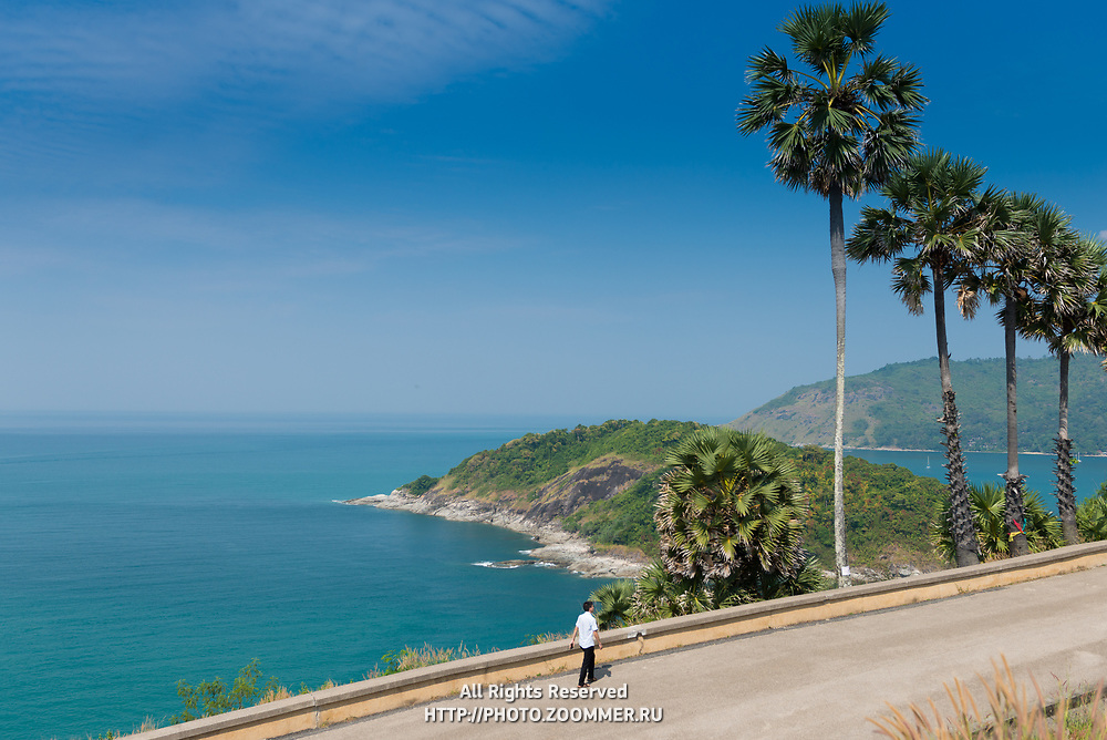 Tourist walking along the sea on Promthep Cape, Phuket, Thailand