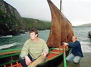 Lorcan Slattery, left,  and Paidi de Hora pictured with a Kerry curragh at  Dun Chaoin Pier in County Kerry.  The Kerrymen hope to make a curragh in New Zealand.<br />Picture by Don MacMonagle<br />Story by Donal Hickey