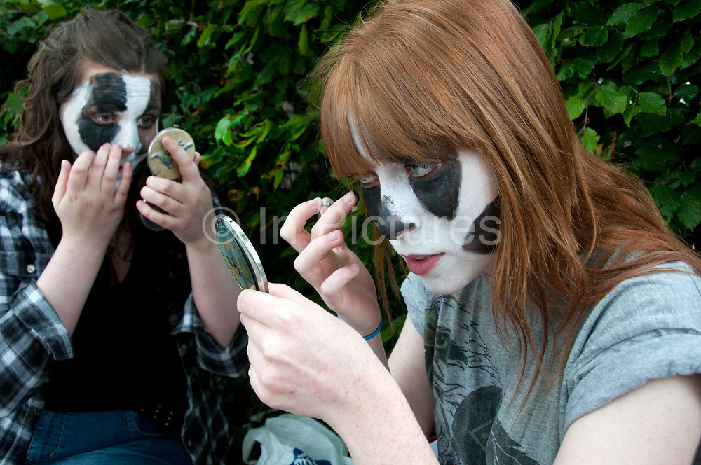 Protest against the proposed cull of badgers June 1st 2013. Two women apply their badger facepaint.