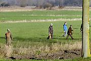 Nederland, Ubbergen, 9-12-2018Een groepje jagers en drijvers lopen op een weiland, op zoek naar klein wild. Terwijl ze naar een volgend stuk lopen worden de eerder afgeschoten dieren, hazen opgeraapt.FOTO: FLIP FRANSSEN