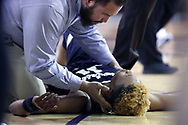 HIGH POINT, NC - JANUARY 06: Charleston Southern's Christian Keeling is tended to by High Point trainer Josh Geruso after he suddenly collapsed to the court late in the game. The High Point University of Panthers hosted the Charleston Southern University Buccaneers on January 6, 2018 at Millis Athletic Convocation Center in High Point, NC in a Division I men's college basketball game. HPU won the game 80-59.