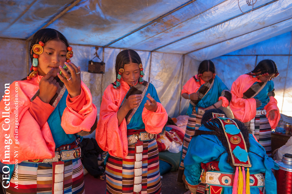 Young women in typically colorful Tibetan costumes primp before their upcoming traditional dance performance at the festival. Nakchu, Tibet