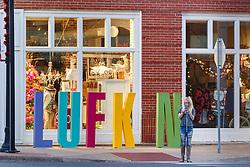 "Tourists with ""Lufkin"" sign, downtown Lufkin, Texas, USA."