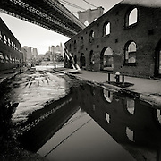 Reflection of the Brooklyn bridge and the Old Tobacco Warehouse in a puddle on Water Street, DUMBO, Brooklyn, 2010.