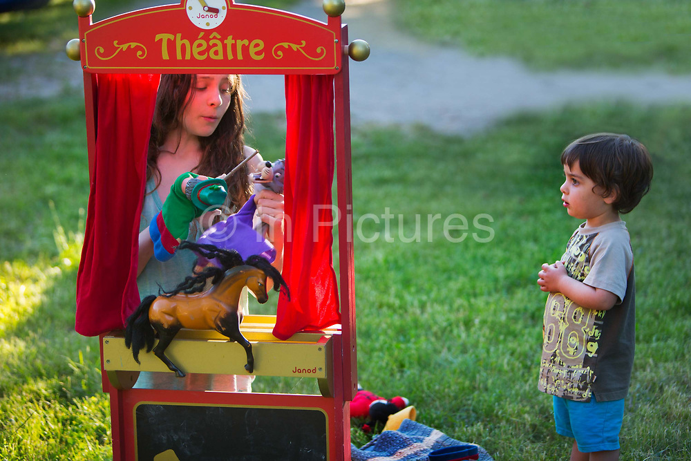 Young children playing with a toy puppet theatre in the French countryside, 5th June 2016,