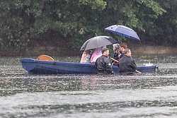 © Licensed to London News Pictures. 04/06/2021. London, UK. Members of a film crew caught in the rain on West Boating Lake in Victoria Park, east London. Photo credit: Marcin Nowak/LNP
