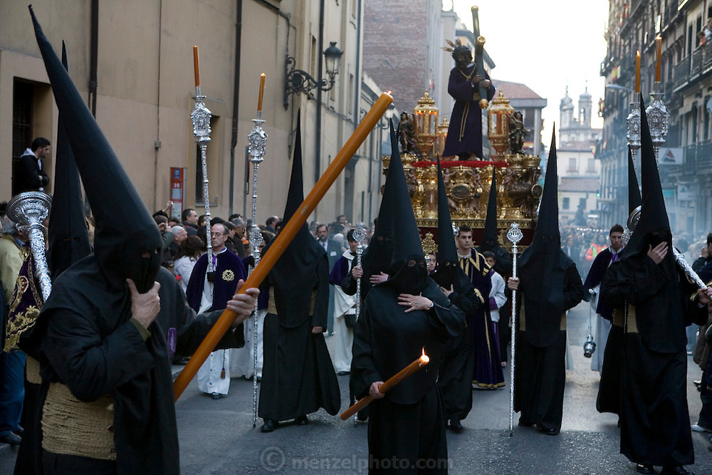 Hooded penitents in a procession during Holy week in Madrid, Spain. Street processions are organized in most Spanish towns each evening, from Palm Sunday to Easter Sunday. People carry statues of saints on floats or wooden platforms, and an atmosphere of mourning can seem quite oppressive to onlookers.