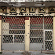 "A closed down Souvlaki bar in Irinis str , Thessaloniki. The sign above predecess the Souvlaki bar and   reads ""Glassware"""
