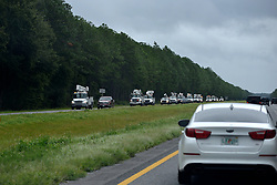 Utility vehicles drive along Interstate 75, near Jacksonville, FL, on September 11, 2017. Flood water resides from parts of Jacksonville, FL after Hurricane Irma took an unexpected turn and caused massive power outages and coastal flooding around the state.