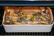 Chicken grilling in an oven with sage and lemon peels