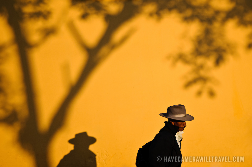 A man walking past a brightly painted yellow stucco wall in Antigua Guatemala casts a strong shadow as he walks under a tree. Famous for its well-preserved Spanish baroque architecture as well as a number of ruins from earthquakes, Antigua Guatemala is a UNESCO World Heritage Site and former capital of Guatemala.