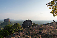 A woman sits at the top of Pidurangala Rock, a mountain peak best known for its excellent view of the famous Sigiriya rock fortress (left of image).