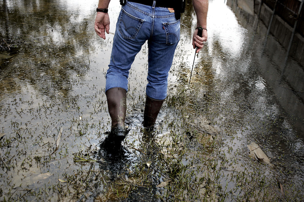 """Bill Sarver of Grand Bay, Alabama, walks with a """"snake protector"""" (knife) as he helps the residents of Sabine Pass, Texas, deal with the aftermath of Hurricane Ike Friday September 19, 2008."""