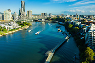 Aerial view of a Citycat ferry cruising by the cycle and pedestrian Riverwalk, Story Bridge & Brisbane City in the background, Brisbane, Queensland, Australia