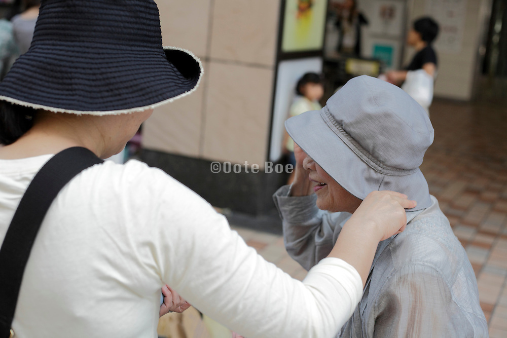 senior woman buying a hat at an outdoors clothing market