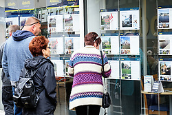 People looking into an estate agents window. UK