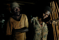 Cosmos Mbawala stands with his wife Halima Salumu inside their hut where they stood when they heard the screams of their son, Cosmos Chakoma, 12, after he was killed by a lion in Hingawali village near Lindi, Tanzania. Cosmos, 12,  had just gone to see a lion that was killed in a nearby village that villagers had thought was responsible for killing others earlier in the month when he was attacked by this lion.  (Ami Vitale)