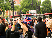 Female Asian tourist wearing Union Jack top hat takes a photo near Parliament Square, Westminster, London