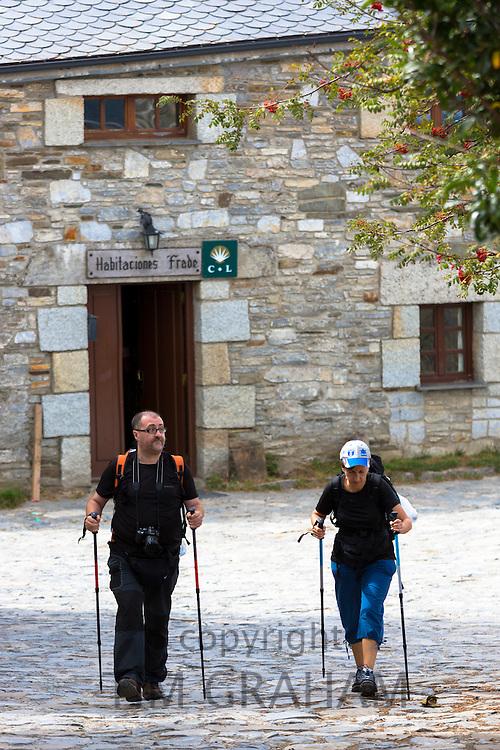Pilgrims setting off from Habitaciones Frade to continue the Camino de Santiago pilgrim route at Triacastela in Galicia, Spain
