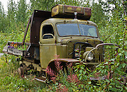 """An old green truck rusts in historic McCarthy. McCarthy and nearby Kennecott Mines National Historic Landmark are nestled under the glacier-clad Wrangell Mountains within Wrangell-St. Elias National Park and Preserve, Alaska, USA. Old mine buildings, artifacts, and colorful history attract summer visitors. Remote McCarthy is connected to Chitina via the McCarthy Road spur of the Edgerton Highway. At the east end of McCarthy Road, visitors must park their vehicle and walk across the footbridge to McCarthy. From McCarthy, a privately-operated shuttle takes visitors 5 miles to Kennecott. After copper was discovered between the Kennicott Glacier and McCarthy Creek in 1900, the Kennecott town, mines, and Kennecott Mining Company were created and named after the adjacent glacier. Kennicott Glacier and River had previously been named after Robert Kennicott, a naturalist who explored in Alaska in the mid-1800s. The corporation and town stuck with a mistaken spelling of """"Kennecott"""" with an e (instead of """"Kennicott"""" with an i). Partly because alcoholic beverages and prostitution were forbidden in the company town of Kennecott, the neighboring town of McCarthy grew quickly to provide a bar, brothel, gymnasium, hospital, and school. The Copper River and Northwestern Railway reached McCarthy in 1911 to haul over 200 million dollars worth of ore 196 miles to the port of Cordova on Prince William Sound. By 1938, the worlds richest concentration of copper ore was mostly gone, the town was mostly abandoned, and railroad service ended. Not until the 1970s did the area began to draw young people for adventure and the big money of the Trans Alaska Pipeline project. Declaration of Wrangell-St. Elias National Park in 1980 drew adventurous tourists who helped revive McCarthy with demand for needed services. Wrangell-St. Elias National Park and Preserve (the largest National Park in the USA) is honored by UNESCO as part of a UNESCO World Heritage Site."""