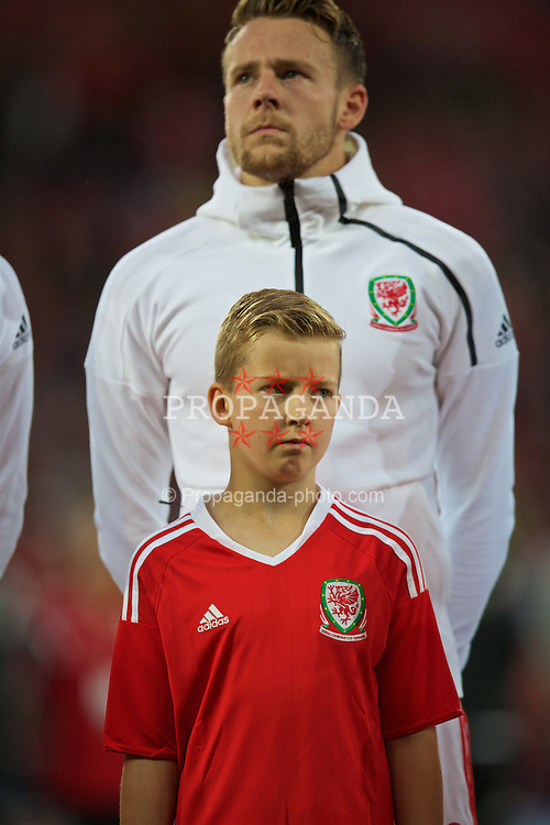 CARDIFF, WALES - Monday, September 5, 2016: A mascot lines-up in front of Wales' Chris Gunter before the 2018 FIFA World Cup Qualifying Group D match against Moldova at the Cardiff City Stadium. (Pic by David Rawcliffe/Propaganda)