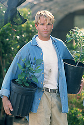 Handsome Gardener holding two potted plants
