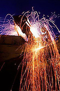 Sparks fly as a welder works to repair heavy construction equipment.