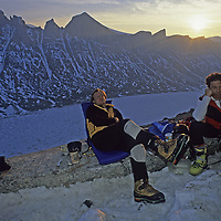 BAFFIN ISLAND, Nunavut, Canada. Jared Ogden & Greg Child (MR) relax in Arctic midnight sunlight after long day climbing high on Great Sail Peak, a huge cliff above frozen lake in Stewart Valley.