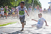 Ryan Sunderland, 8, races through a Slip 'n Slide at the 2012 Bolder Boulder 10K road race in Boulder, Colorado.