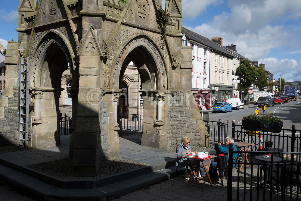 Ladies have tea in afternoon sunshine beneath the clocktower in Machynlleth, on 12th September 2018, in Machynlleth, Powys, Wales. To celebrate the 21st birthday of Viscount Castlereagh, the townspeople subscribed to the erection at the towns main road intersection of the clock tower, which has become widely known as the symbol of Machynlleth. The tower, which stands on the site of the old town hall, is the first thing many visitors will notice. The foundation stone was laid on 15 July 1874.