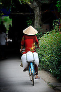Woman on bicycle wearing traditional conical hat (Non La). Mekong River in Cai Be, Tien Giang Province, Vietnam