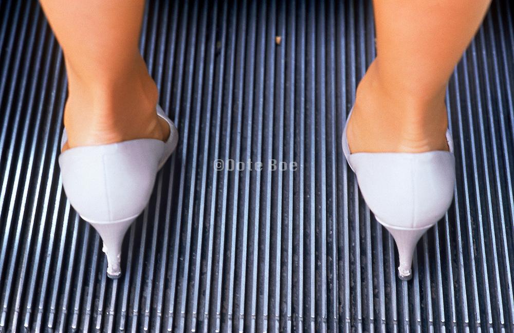 Woman wearing white pumps standing on an escalator