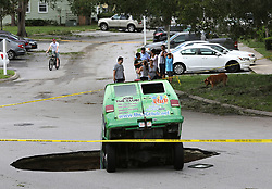 Residents survey the scene of a van in a sinkhole on Monday, September 11, 2017, that opened up at the Astor Park apartment complex in Winter Springs, FL, USA, during Hurricane Irma's passing through central Florida Sunday night. The glass on the ground is the window that the driver punched out to extract himself after driving into the sinkhole. Photo by Joe Burbank/Orlando Sentinel/TNS/ABACAPRESS.COM