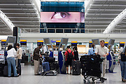 "A scene of busy modern air travel as international passengers check-in at the British Airways Heathrow Airport's Terminal 5. Under the gaze of a giant eye that seems to be peering from out of a massive TV screen, the self-service kiosks that have been developed to allow customers to process their own ticketing on arrival at this aviation hub for British Airways. Once they've chosen their seat and printed a boarding pass, they can go straight to the Fast Bag Drop desk at the airport. There, baggage will be tagged by an agent and sent to the aircraft. At a cost of £4.3 billion, Terminal 5 has the capacity to serve around 30 million passengers a year. From writer Alain de Botton's book project ""A Week at the Airport: A Heathrow Diary"" (2009). ..."