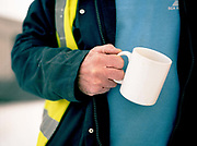 A lorry driver holds a mug of tea at The Pitstop burger van on the 29th April 2010 in Benhall in the United Kingdom.