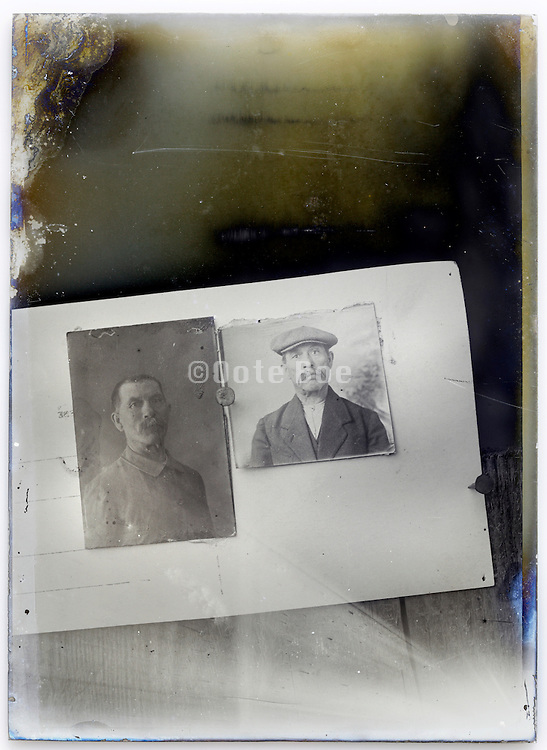 eroding glass plate with photographed reproduction of two male portraits