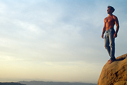 shirtless man standing on the edge of a cliff overlooking Southern California