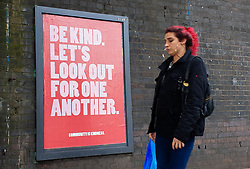© Licensed to London News Pictures. 30/03/2020. London, UK. A woman walks past a 'Be Kind. Let's Look out for one Another.' sign in north London as  coronavirus lockdown continues.  Photo credit: Dinendra Haria/LNP