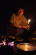 The porter and cook for a three day trek in the mountains surrounding Kalaw, Burma (Mvvvyanmar) prepares supper by candlelight.