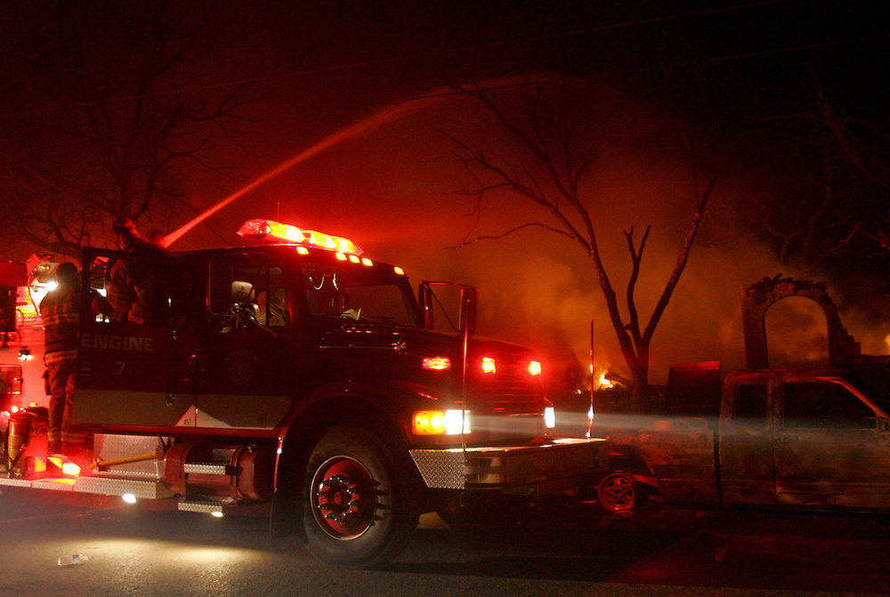 Photo © 2005 Alex Jones..A Brady fire department truck sprays water on a burning structure on Avenue E Tuesday night, December 27, 2005, in Cross Plains, Texas after a massive fire swept through the town.