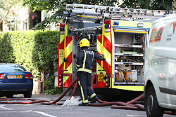 A firefighter next to an appliance in Grenfell Road, close to the scene of a fire that has engulfed the 24-storey Grenfell Tower in west London.