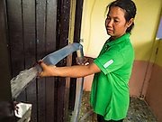 10 MAY 2016 - TA TUM, SURIN, THAILAND: A woman at the public school in Ban Khana fills the water cisterns with water from the artesian well in Ta Tum, Surin, Thailand. The school hasn't had running water for about one month. The well is the most important source of drinking water for thousands of people in the communities surrounding it.  In the past many of the people had domestic water piped to their homes or from wells in their villages but those water sources have dried up because of the drought in Thailand. Thailand is in the midst of its worst drought in more than 50 years. The government has asked farmers to delay planting their rice until the rains start, which is expected to be in June. The drought is expected to cut Thai rice production and limit exports of Thai rice. The drought, caused by a very strong El Nino weather pattern is cutting production in the world's top three rice exporting countries:  India, Thailand and Vietnam. Rice prices in markets in Thailand and neighboring Cambodia are starting to creep up.    PHOTO BY JACK KURTZ