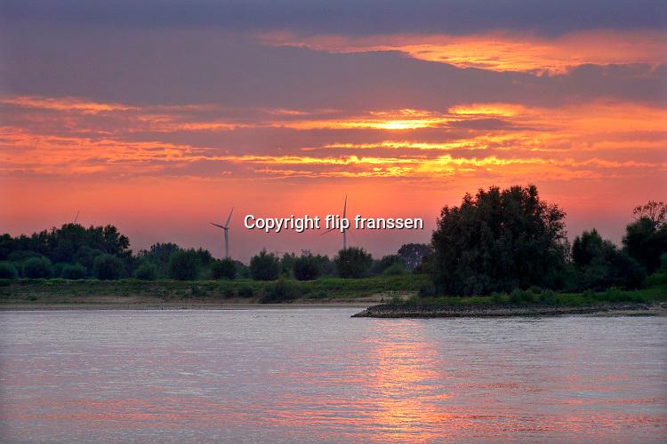 Nederland, Nijmegen, 18-7-2020 Ondergaande zon vanuit de Ooijpolder richting Lent aan de overkant van de rivier de Waal .Windmolens zijn te zien. Foto: ANP/ Hollandse Hoogte/ Flip Franssen